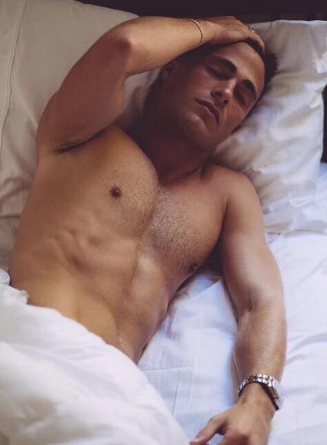 man sleeping in bed shirtless