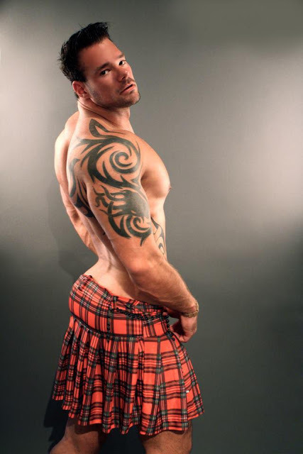 shirtless man wearing a kilt and showing his butt