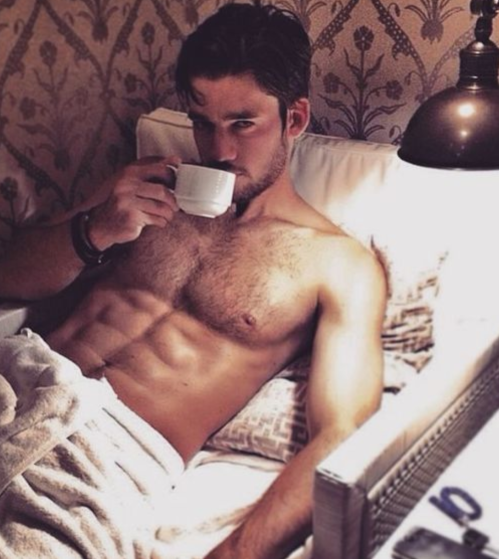 handsome guy drinking coffee in bed
