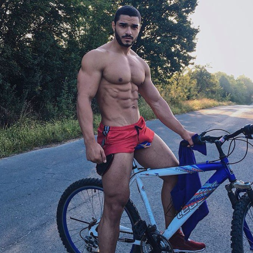 shirtless handsome guy on a bike, red shorts, hunk